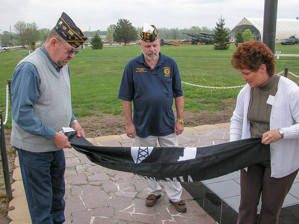 Post 233 officer Larry Whitlock and Atterbury public affairs representative fold POW flag while 7th. District representative Herb Hoffman looks on.