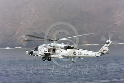 HM - SH-60USN 00004 A US Navy Sikorsky SH-60 Seahawk HS-15 seen flying over a body of water and a coastline, by Peter J Mancus