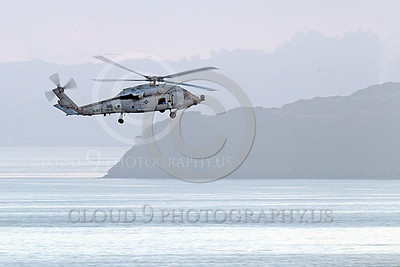 HM -  SH-60USN 00028 A US Navy Sikorsky SH-60 Seahawk HS-15 seen flying and banking low over a body of water and a coastline, by Peter J Mancus