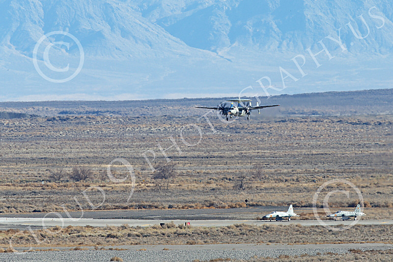 E-2USN 00280 A Grumman E-2 Hawkeye US Navy lands at NAS Fallon with aggressor aircraft waiting to take the runway 1-2015 military airplane picture by Peter J Mancus