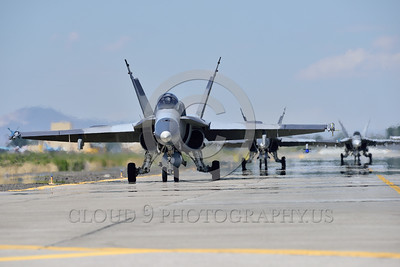 F-18A-USN-0002 A USN McDonnell Douglas F-18A Hornet taxis for take-off at NAS Fallon 4-2016 ahed of two Boeing F-18 Super Hornet military airplane picture by Peter J  Mancus