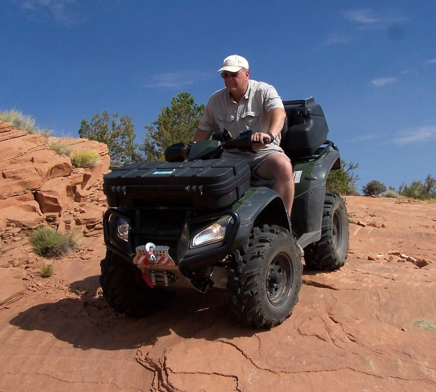 """The versatility of the ATV in aviation archaeology is unmatched. With a short narrow wheel base and four wheel drive capabilities, I can maneuver over and around obstacles that a truck or jeep could never do. <br /> <br /> The ATV I use is a modified 2005 Honda Rincon 650 4x4 with independent suspension. It is equipped with two GPS receivers, 2 meter/440 mhz communications, 2.0 Warn winch, 2"""" lift, full protective under armor, front and rear heavy duty bumpers, front and rear cargo lockers, on-board air compressor, ITP wheels and over-sized traction tires. It can climb 50 degree slopes. Top speed on level ground is 55 mph."""