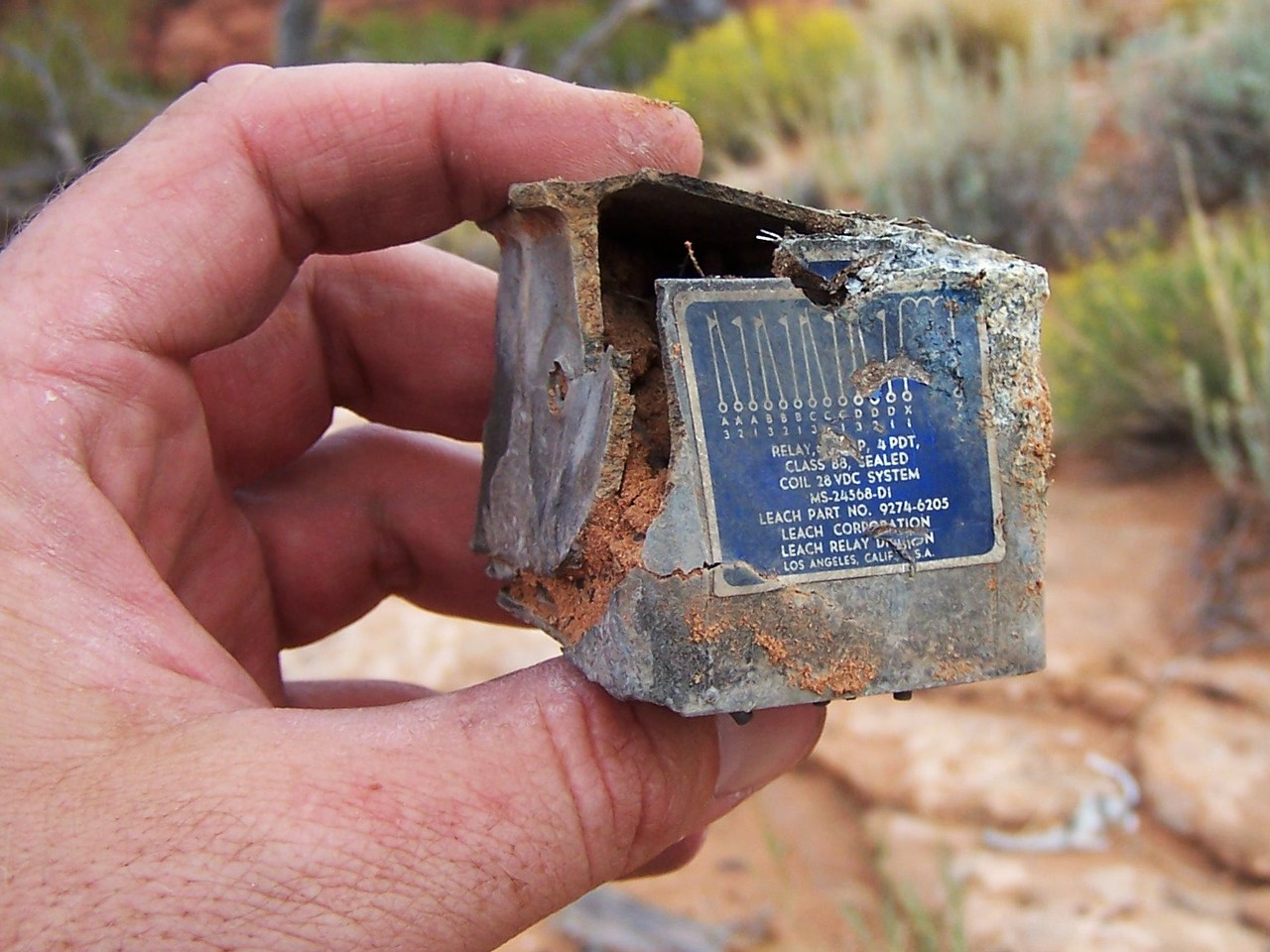 A burned electrical relay was found partially buried in the sandy surface.