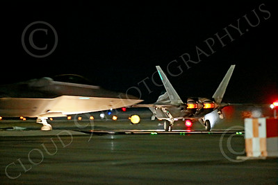 AB-F-22 00089 A Lockheed F-22 Raptor stealth jet fighter USAF taxis toward Nellis AFB's runway during a night Red Flag mission as another takes off in afterburner 7-2014 military airplane picture by Peter J Mancus