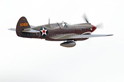 WB - Curtiss P-40 00098 A flying, olive drab, sharkmouth Curtiss P-40 Warhawk American WWII era fighter with an external fuel tank, by Peter J Mancus
