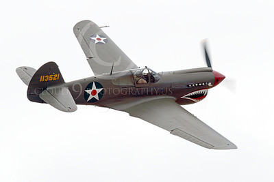 WB - Curtiss P-40 00070 A flying, olive drab, sharkmouth Curtiss P-40 Warhawk American WWII era fighter airplane picture, by Peter J Mancus