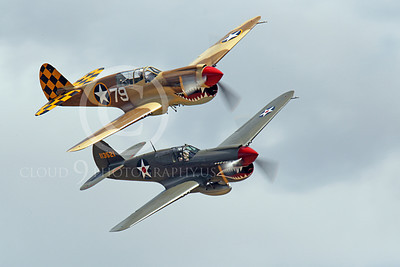 WB - Curtiss P-40 00096 Two sharkmouth Curtiss P-40 Warhawks fly in close formation in front of clouds, by Peter J Mancus