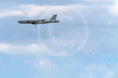 OR 00003 A USAF Boeing B-52 Stratofortress bomber drops a sring of high explosive bombs with  parachutes to delay their descent and impact, by Peter J Mancus