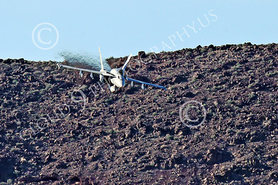 MLLF 00005 A Boeing F-18E Super Hornet jet fighter, US Navy, flies low over a ridge line into a canyon on a training mission, military airplane picture by Peter J Mancus