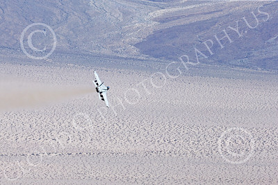 MLLF 00021 A Boeing EA-18G Growler, electronics warfare jet, US Navy, VX-9 VAMPIRES, XE code, banks right low over a vast desert on a training mission, military airplane picture by Peter J Mancus