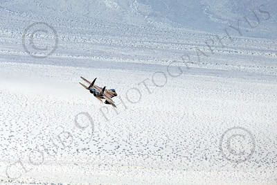 MLLF 00026 A brown McDonnell Douglas F-15 Eagle jet fighter, Califronia ANG 144th FIS GRIFFONS, flies low over a vast desert on a training mission, military airplane picture by Peter J Mancus