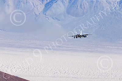 MLLF 00016 A Boeing EA-18G Growler, electronics warfare jet, US Navy, VX-9 VAMPIRES, XE code, in afterburner, flies over a vast desert terrain on a training mission, military airplane picture by Peter J Mancus