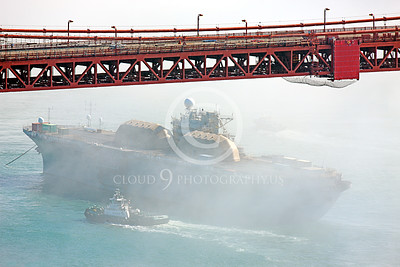 USNWS 00108 An unknown name USN amphibious assault ship, probably LPH Iwo Jima class, undergoing modernization, seen towed into San Francisco Bay under the Golden Gate Bridge, by Peter J Mancus
