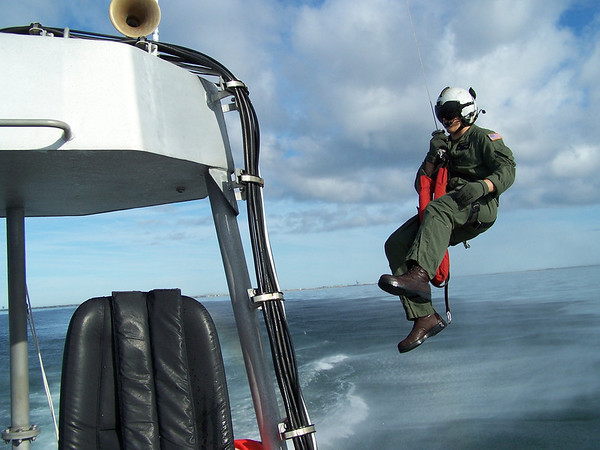 US Navy Corpsman being lowered from a rescue helo to a US Coast Guard boat during exercises off the coast of NC. 2008