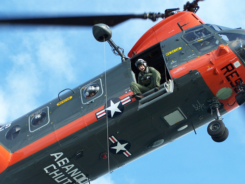 "USMC ""Pedro"" rescue CH-46 helicopter hovers over a USCG boat during joint exercises. 2008. The words ""ABANDON CHUTE"" remind downed pilots to ditch their parachute during rescue to avoid it from getting tangled with hoist gear."
