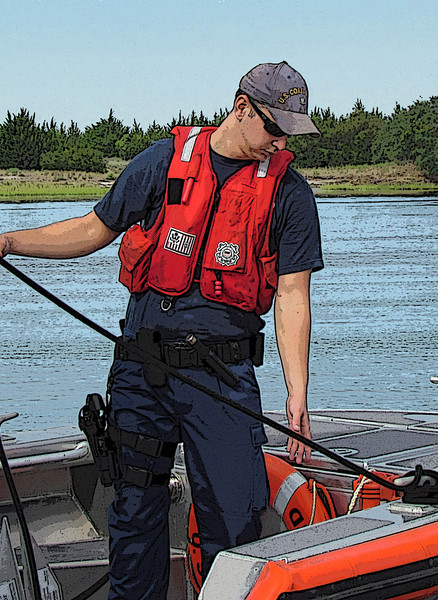 A Coast Guard Petty Officer handles lines while tying up to another boat during a routine safety boarding. Emerald Isle, NC. 2011