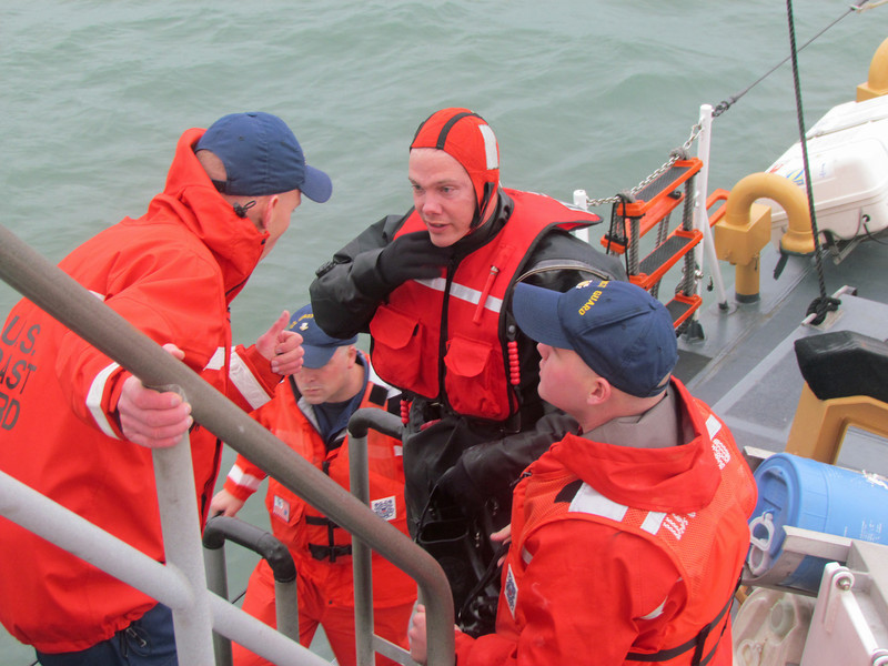 A US Coast Guard rescue swimmer gets last minute instructions prior to entering the water aboard the Cutter Block Island. Morehead City, NC. January 2012.