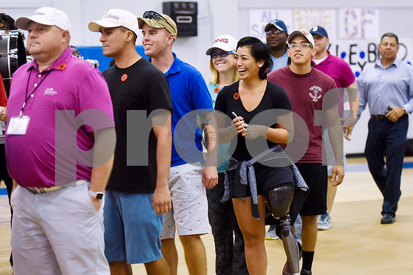 Participants of the Wounded Warriors program walk in during a program honoring Wounded Warriors at All Saints Episcopal School in Tyler, Texas, on Friday, Sept. 29, 2017. Students and faculty dressed in red white and blue, waved American flags and sang patriotic tunes to honor the Wounded Warriors. (Chelsea Purgahn/Tyler Morning Telegraph)