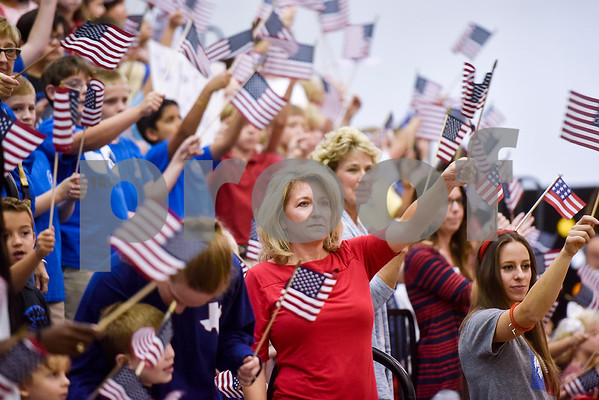 Faculty and students wave American flags during a program honoring Wounded Warriors at All Saints Episcopal School in Tyler, Texas, on Friday, Sept. 29, 2017. Students and faculty dressed in red white and blue, waved American flags and sang patriotic tunes to honor the Wounded Warriors. (Chelsea Purgahn/Tyler Morning Telegraph)