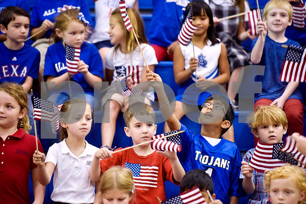 Raj Kumar, 7, second from bottom right, waves an American flag during a program honoring Wounded Warriors at All Saints Episcopal School in Tyler, Texas, on Friday, Sept. 29, 2017. Students and faculty dressed in red white and blue, waved American flags and sang patriotic tunes to honor the Wounded Warriors. (Chelsea Purgahn/Tyler Morning Telegraph)