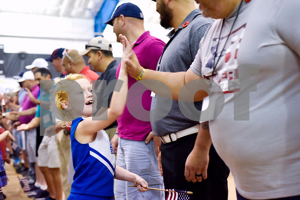 Olivia Preston, 7, high fives veterans during a program honoring Wounded Warriors at All Saints Episcopal School in Tyler, Texas, on Friday, Sept. 29, 2017. Students and faculty dressed in red white and blue, waved American flags and sang patriotic tunes to honor the Wounded Warriors. (Chelsea Purgahn/Tyler Morning Telegraph)