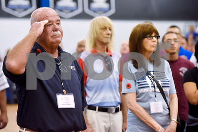 Ron Nash salutes as the national anthem is sung during a program honoring Wounded Warriors at All Saints Episcopal School in Tyler, Texas, on Friday, Sept. 29, 2017. Students and faculty dressed in red white and blue, waved American flags and sang patriotic tunes to honor the Wounded Warriors. (Chelsea Purgahn/Tyler Morning Telegraph)