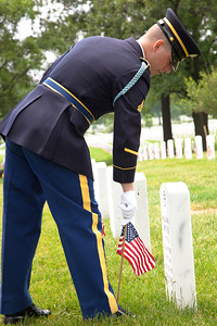 """America's most recent war dead lie in a quiet patch of ground at Arlington National Cemetery known as Section 60. More than 350,000 American Flags decorate the graves at Arlington National Cemetery in preparation for Memorial Day weekend. Here a soldier from the U.S. Army's 3rd Infantry Regiment, """"the Old Guard"""" straightens one of these flags. Friday May 28, 2010 (Photo by Jeff Malet)"""