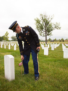 "America's most recent war dead lie in a quiet patch of ground at Arlington National Cemetery known as Section 60. More than 350,000 American Flags decorate the graves at Arlington National Cemetery in preparation for Memorial Day weekend. Here a soldier from the U.S. Army's 3rd Infantry Regiment, ""the Old Guard"" straightens one of these flags. Friday May 28, 2010 (Photo by Jeff Malet)"