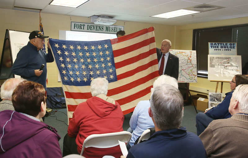 Talk on Battle of the Bulge in WWII, in its 75th anniversary year, at the Fort Devens Museum. Joe Landry, 96, of Shirley, who was a truck driver in the Battle of the Bulge, and Chris de Marcken, 92, of Worcester, who was an American teenager living in Belgium during WWII, hold up an American flag made secretly by de Marcken's mother during the German occupation. She mistakenly made the stars upside down. (SUN/Julia Malakie)