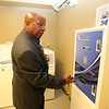 Bedford Green, housing for homeless and at-risk veterans, on the campus of the Edith Nourse Rogers Memorial Veterans Hospital in Bedford. Resident Michael Sexton shows the machine for adding value to a laundry card (works like a Charlie Card on the T), with the card being used in the washers and dryers. (SUN/Julia Malakie)