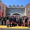 Ribbon cutting and opening ceremony for Bedford Green, housing for homeless and at-risk veterans, on the campus of the Edith Nourse Rogers Memorial Veterans Hospital in Bedford. Elizabeth Collins, VP of Development at Peabody Properties, Inc., with scissors, and other officials, cut the ribbon. (SUN/Julia Malakie)