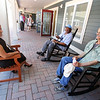 Bedford Green, housing for homeless and at-risk veterans, on the campus of the Edith Nourse Rogers Memorial Veterans Hospital in Bedford. From left, residents Elva Alvarado, a Navy veteran, and Stance Cocroft, an Army veteran, and Army veteran Ralph DeGregorio of Arlington, who is Alvarado's boyfriend, sit on the veranda. (SUN/Julia Malakie)