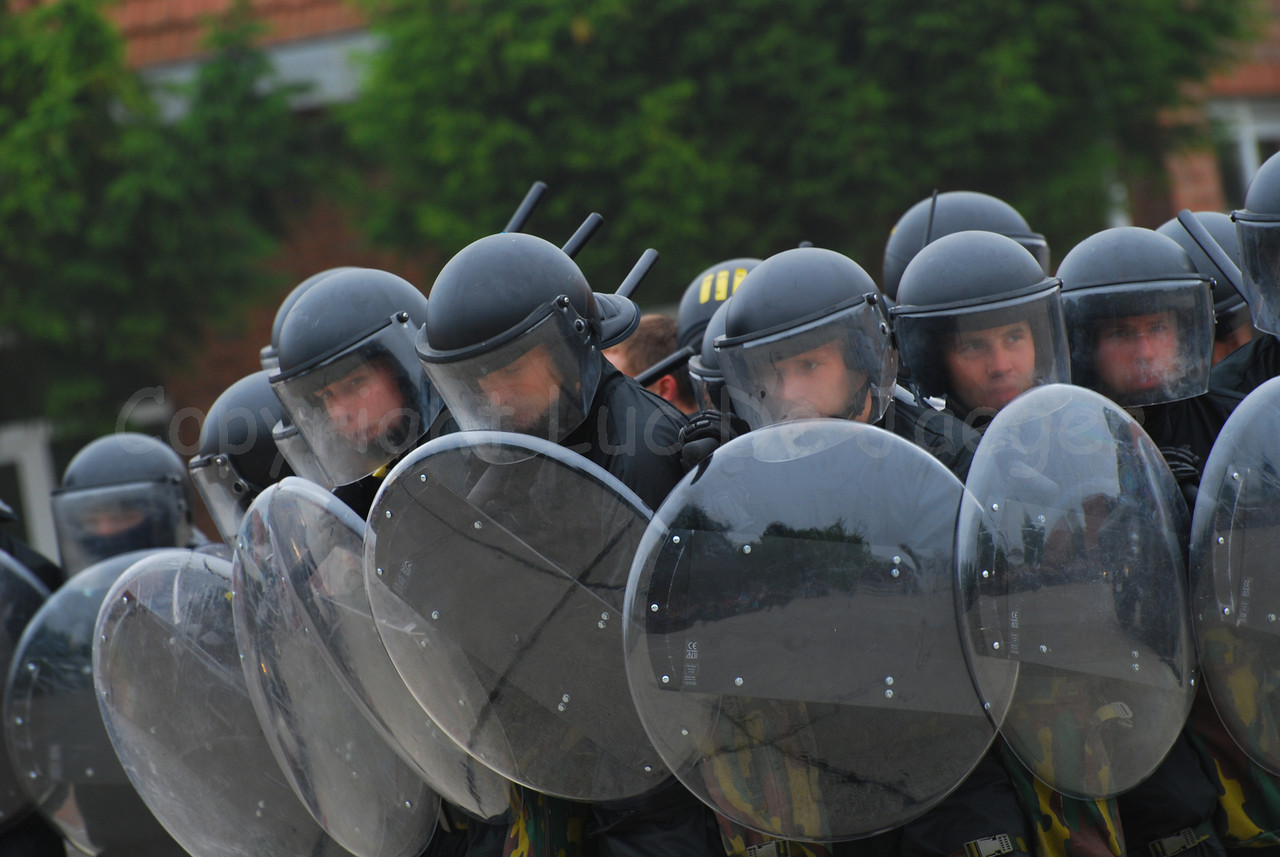 Belgian infantry soldiers in full riot gear in action.