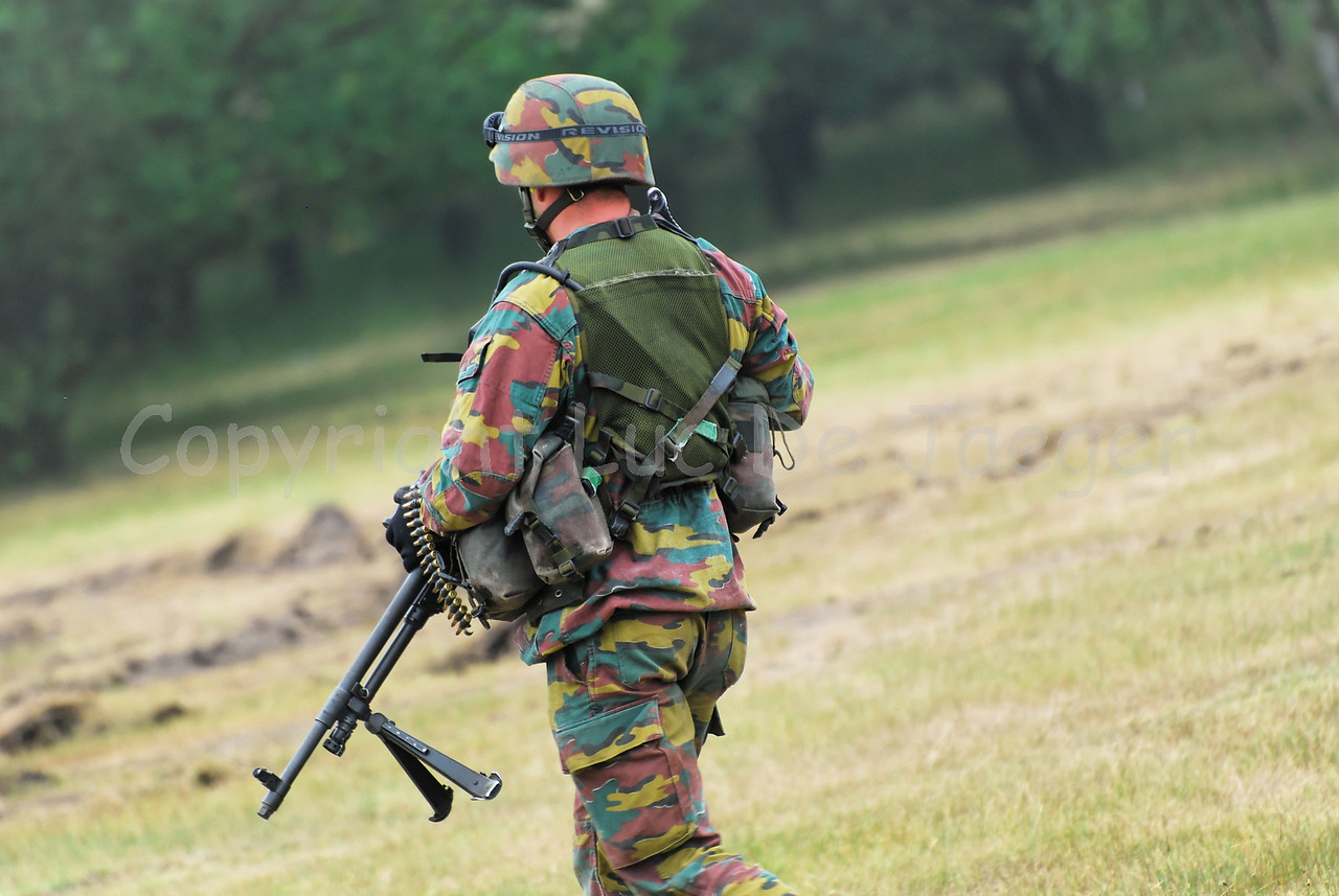 An infantry soldier of the Belgian Army in the fields and handling the FN Minimi rifle.