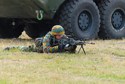 A Belgian Infantry soldier handling the FN Minimi beside the AIV Piranha IIIC.