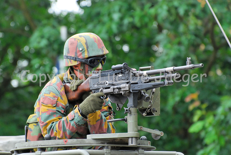 An infantry soldier aiming the FN MAG machine gun on top of the cabin of an Unimog vehicle. The soldier wears goggles by Revision Eyewear.