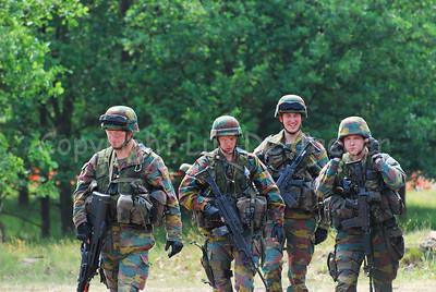 Belgian infantry soldiers in full gear advancing in the fields.