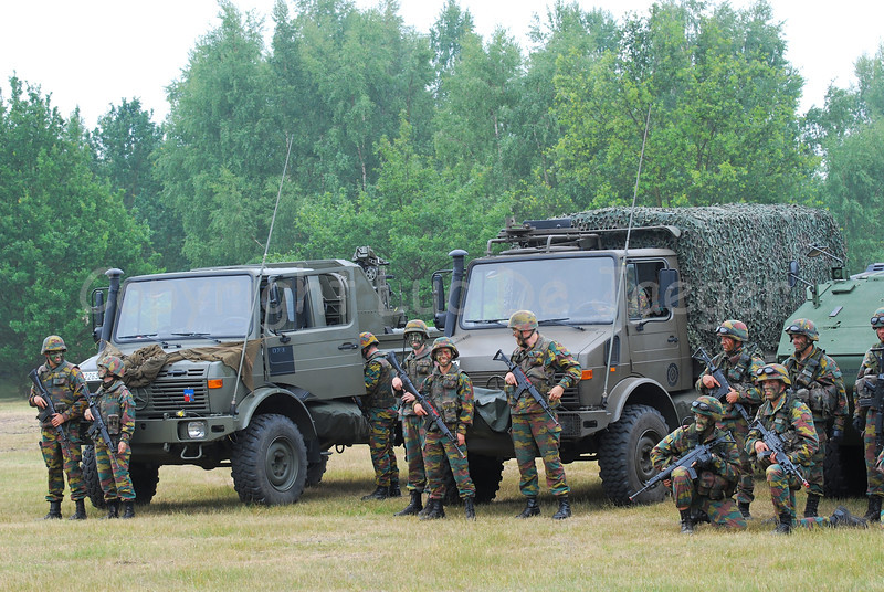 Soldiers of the Belgian Army posing along their Unimog vehicles. To the left is a Mistral launcher section, in the center an artillery section.