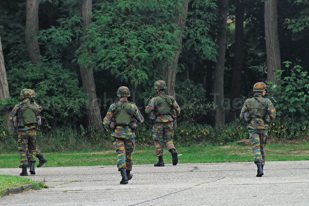 Infantry soldiers of the Belgian Army in training along the road. They all wear goggles by Revision Eyewear and handle FN (assault) rifles.