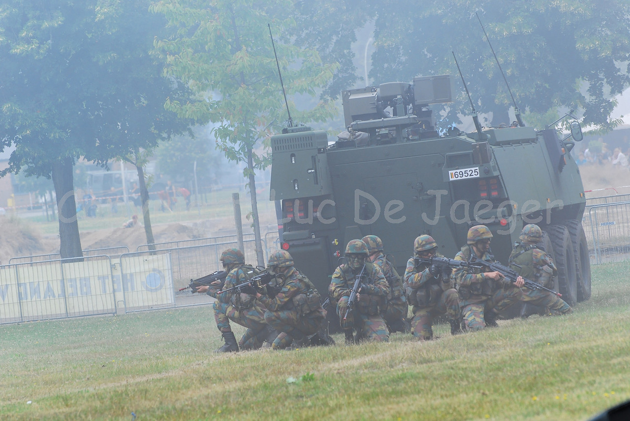 An infantry section of the Belgian Army under cover beside their AIV (Armoured Infantry Vehicle) Piranha IIIC.