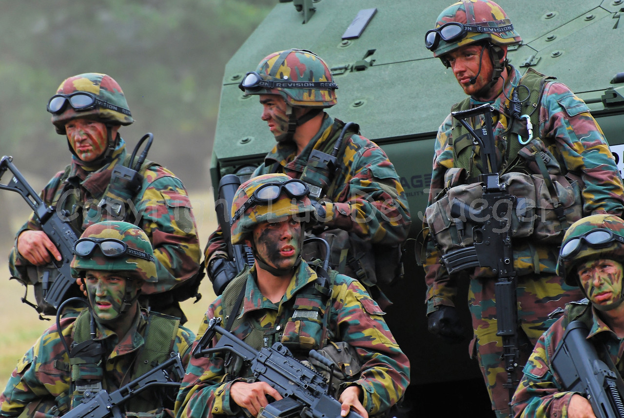 Infantry soldiers of the Belgian Army infront of the AIV Piranha IIIC . The soldiers all wear goggles by Revision Eyewear and handle FN (assault) rifles.
