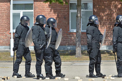 Belgian infantry soldiers in riot gear during a session riot and crowd control. The 2 soldiers on the right wear a different riot helmet.