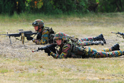 Belgian infantry soldiers in the fields aiming their FN rifles. The soldier is front is handling the FN FNC rifle while the soldier behind handles the FN Minimi.