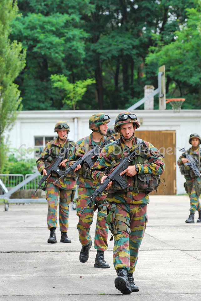Soldiers of a Belgian infantry section on patrol with their FNC rifles in front of them. They wear Revision goggles.