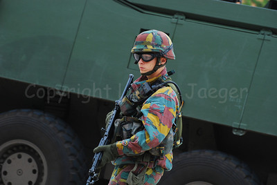An infantry soldier in front of the AIV handles the FN FNC assault rifle and wears goggles by Revision Eyewear.