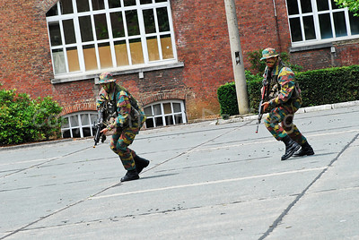 Paratroopers running and turning back to eventually seek cover.