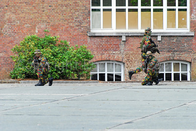 Paratroopers on the guard while another one is running to seek cover.