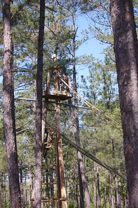 MSG Turk is just visible, standing on the platform behind the rope, as he prepares to slide down to the end of this obstacle