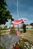 Fitchburg Police Ptl. Josh Lambert, (far right), Fitchburg H.S. Resource Officer, raises the American flag with FHS students Alexis Luman (left) and Alize Rios, (obscured) on a flagpole erected  in honor of LCpl Geoffrey Cayer, killed in Iraq in 2006. The flagpole sits next to the Marine's Memorial at Boulder Dr and Main St. SENTINEL & ENTERPRISE/Jim Marabello