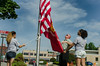 Fitchburg Police Ptl. Josh Lambert, (middle), Fitchburg H.S. Resource Officer, raises the flag of the U.S. Marines with FHS students Alize Rios (left) and Alexis Luman (right) on a flagpole erected  in honor of LCpl Geoffrey Cayer, killed in Iraq in 2006. The flagpole sits next to the Marine's Memorial at Boulder Dr and Main St. SENTINEL & ENTERPRISE/Jim Marabello